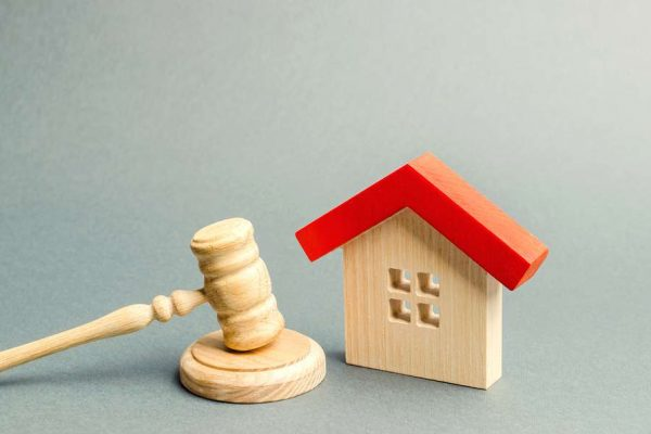 Miniature of a home and a gavel. Conveyancing concept